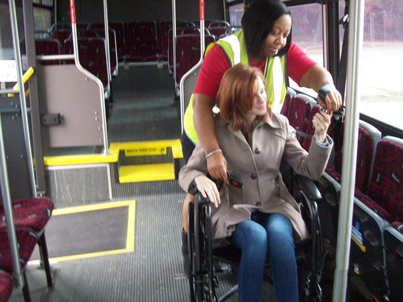 A Wolfline employee helps a woman in a wheelchair access the bus.